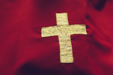 Gold cross on a red background