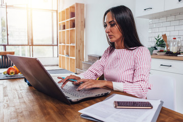 Woman sitting at home work station and typing on laptop