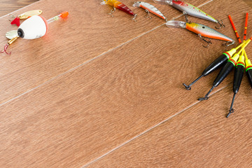 Frame fishing tackle - fishing spinning, hooks and lures on light wooden background. Top view