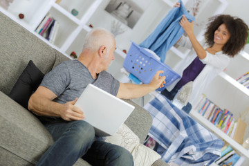 elderly man with young woman using internet at home