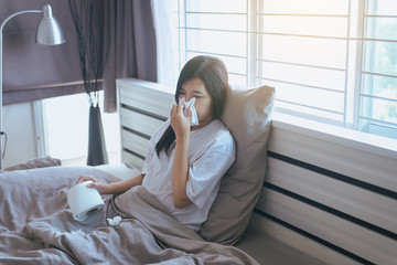 Young asian woman with cold blowing and runny nose on bed,sick female sneezing,Concept of health