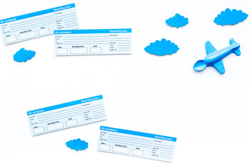 Family trip concept. Airplan toy, clouds, airplan tickets on white background top view copy space