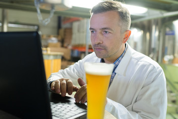 brewer working with laptop at the manufacturing