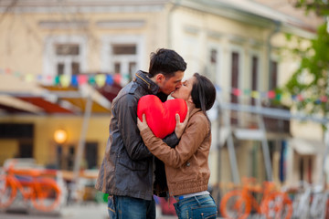 Young couple with heart shape toy kissing