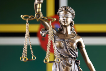 Symbol of law and justice with Dominica Flag. Close up.