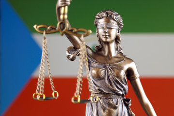 Symbol of law and justice with Equatorial Guinea Flag. Close up.