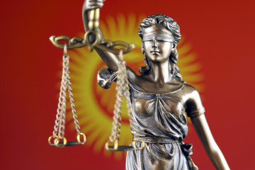 Symbol of law and justice with Kyrgyzstan Flag. Close up.