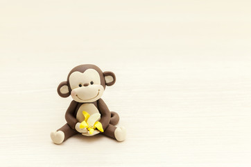 Foto op Aluminium Aap little monkey toy sitting with a banana