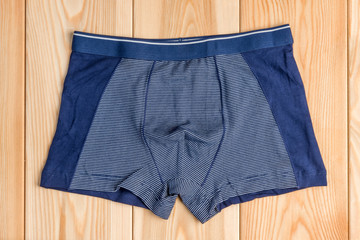 blue new cotton panties for boy clothes on wooden boards top view