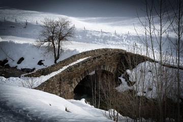 old stone bridge in snowy landscape