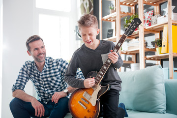 Son and father playing electric guitar at home