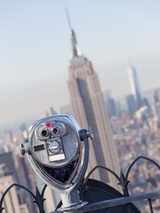 Wall Mural - New York City, USA. Vintage tourist binoculars at Top of the Rock observation deck in front of Manhattan downtown skyline with Empire State Building and skyscrapers at sunset.