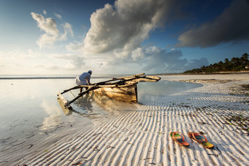 Fotobehang Zanzibar Fishermen going on ocean on traditional fishing boat in Zanzibar with storm clouds at sunrise
