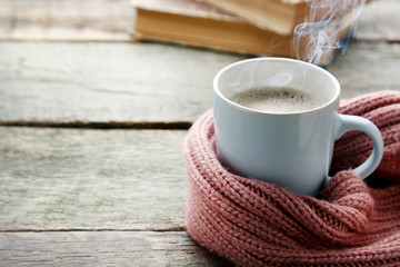 Cup of coffee with pink scarf on wooden table