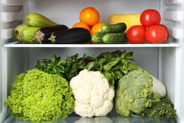 Open fridge full of vegetables