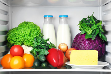 Open fridge full of vegetables with cheese and bottle of milk