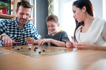 Happy family playing board game at home