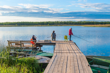 family on a fishing trip on a pier in the background of a picturesque lake