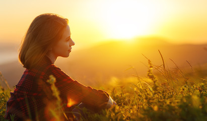 Woman sits with her back in the field and look sunset in the mountains