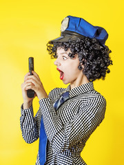 A girl with a gun holding a pistol looks playfully at the barrel of the gun on a yellow background.