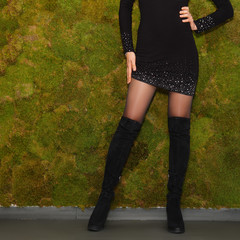 Long female legs in thin black tights high boots