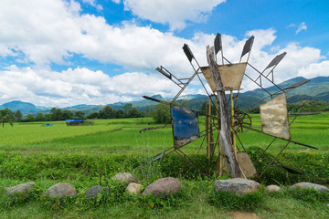Wood turbine in the water beside rice field with blue sky and clouds background.