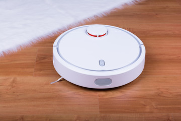 Vacuum cleaner robot on laminate wood floor.