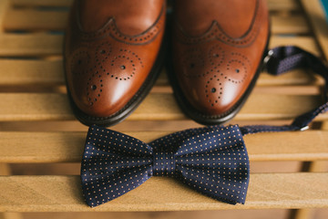A pair of brown stylish leather men's brogues shoes on a chair beside a blue bow tie. Accessories for the groom