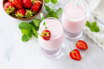 Fresh strawberry smoothie and fresh strawberries on a gray stone or slate background. Vegan dish. Proper nutrition. Healthy lifestyle. Copy space.