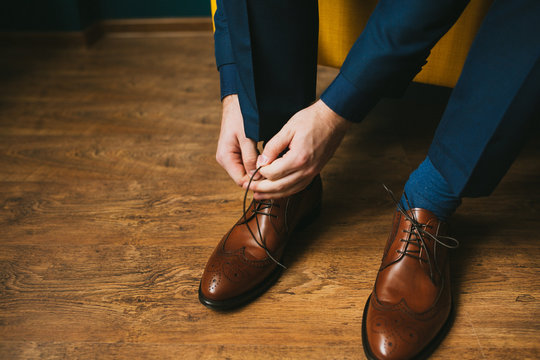A man or a groom in a blue suit ties up shoelaces on brown leather shoes brogues on a wooden parquet background