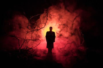 strange silhouette in a dark spooky forest at night, mystical landscape surreal lights with creepy man. Toned Wall mural