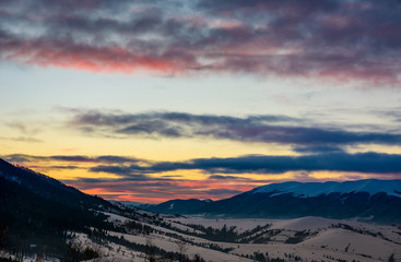 gorgeous colorful clouds over the mountain ridge. beautiful sky at winter dawn