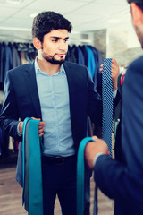 Customer man is picking up tie for jacket in front of the mirror
