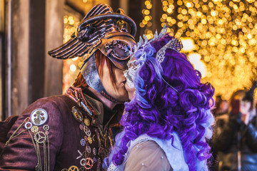 VENICE, ITALY - FEBRUARY 10 2018: Kiss between two carnival masks dressed with imaginative patterns