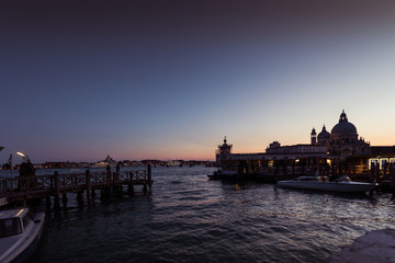 VENICE, ITALY - FEBRUARY 10 2018: vaporetto terminal  at sunset in front of Basilica della Salute. The vaporetto is the public means par excellence of the city