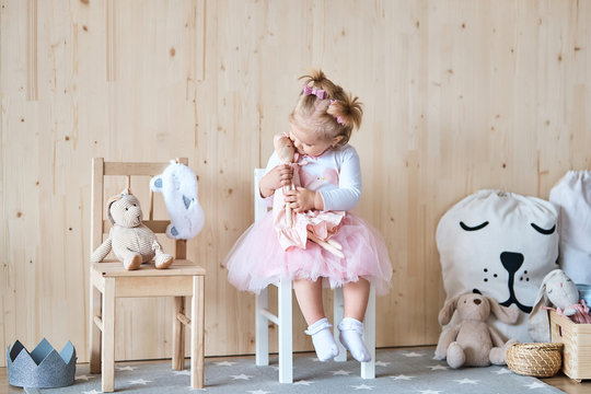 Amazing little girl playing with a doll in her room