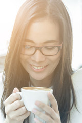 Beautiful asian attractive woman has holding and drinking a coffee at coffee cafe in the morning with happy and relaxing time.