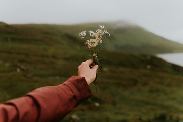 Woman wearing a red rain jacket holding a flower bouquet in front of a green field bokeh unsharp background in Scotland, UK