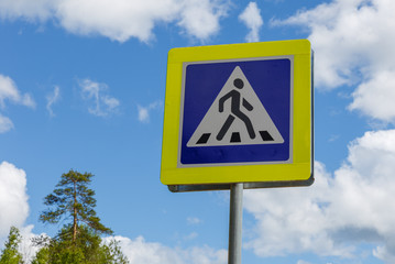 sign of a pedestrian crossing against the blue sky