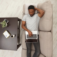 Concenrated young man using laptop at home