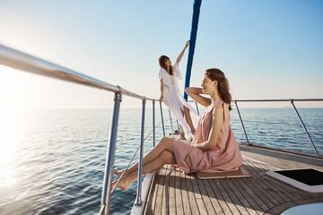 Outdoor shot of tender and attractive adult female, spending time on boat. Girl stands on bow of yacht with dreamy look while her friend sits at side, both feeling like in paradise