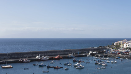 Panoramic view from nearby hill of the harbor, protected by a large wall, marina and the picturesque town of Playa de San Juan