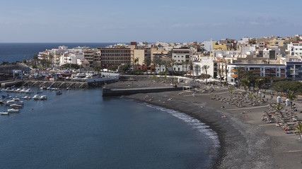 Vantage views towards the harbor, town and the small beach of black sand, lapilli and pebbles, populated all year round