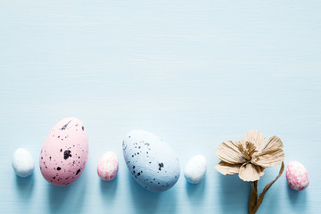 Easter eggs and decorative paper flowers on light blue background, top view, copy space