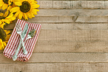 Picnic Table Place Setting with Pretty Yellow Sunflowers, Silverware, red and white checked Napkin, brown Rustic Wood Board Background with empty room or space for copy, text, or your words or design.