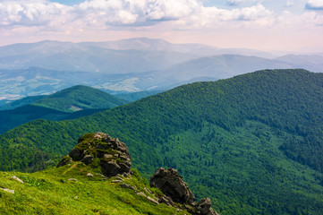grassy hillside over the cliff in mountains. magnificent Borzhava mountain ride in the distance. viewing location mountain Pikui. gorgeous landscape of Carpathians