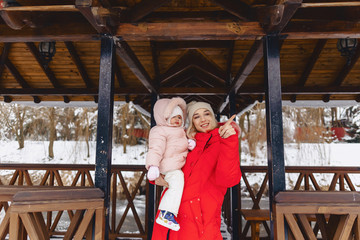mother with baby walking picturesque country cottage in