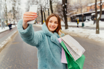Inspired brown-haired girl making selfie after shopping and laughing. Stylish caucasian female shopaholic holding bags and taking picture of herself at winter time.