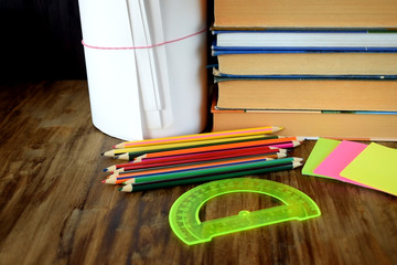 Set of coloured pencils, stickers, books and protractor on a wooden table