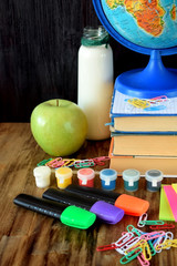 A pile of books, globe, paints, paper clips, highlighters, a green apple and a jar of milk on a wooden table